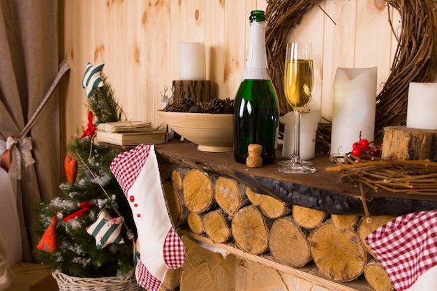 Still life of rustic log mantle with wine, stockings and christmas decorations