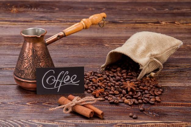 ポットとシナモンが入ったコーヒー豆の静物画の袋