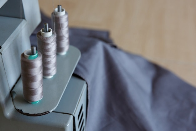 Натюрморт. швейные принадлежности. нитки и ткань для оверлока