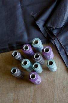 Натюрморт. швейные принадлежности. нитки и ткань лежат на деревянном столе
