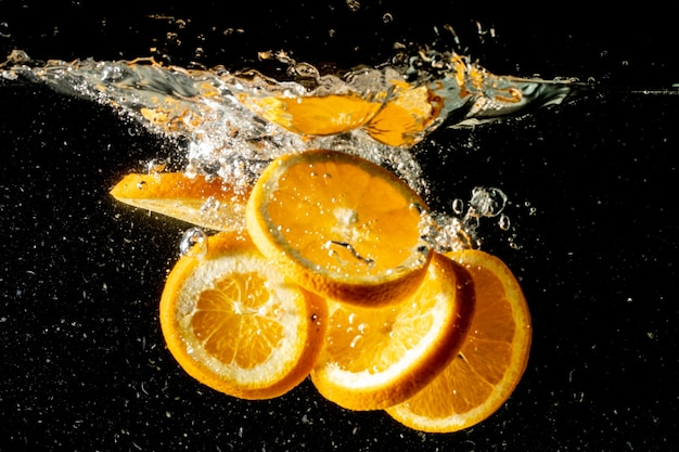 Still life shot of orange slices falling under the water and making a big splash