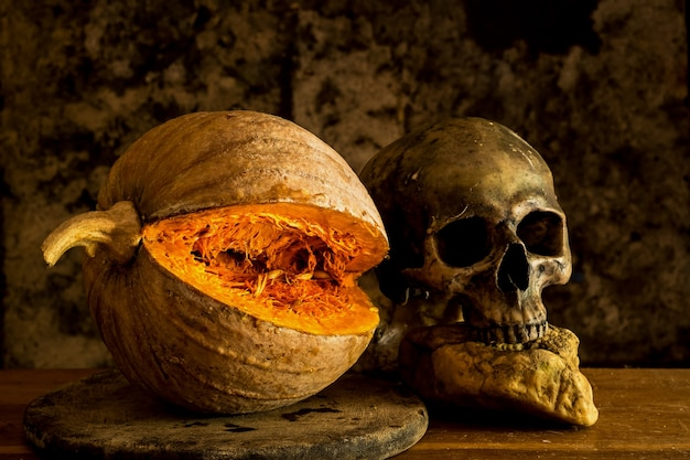 Still life skull and pumpkin on the table. a symbol of halloween