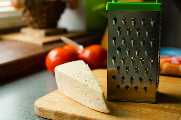 キッチンの木製ボードにスチールおろし金で新鮮でおいしいチーズの静物ストックフォト。料理のコンセプト。背景にぼやけた赤いトマト。