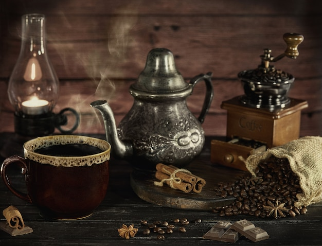 Still life in the style of an old photograph with a coffee grinder, coffee beans with an old lamp and a kettle with a cup with steam