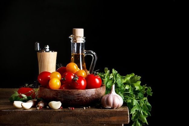 Still life of tomatoes, garlic and olive oil on wooden boards.