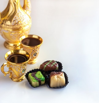 Still life traditional golden arabic coffee set with dallah, cup and chocolate candy.