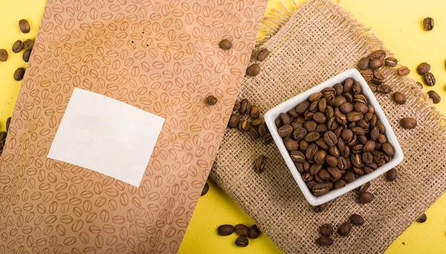 Still life of unbranded coffee packaging in different colors and natural backgrounds next to cups coffee pot and coffee