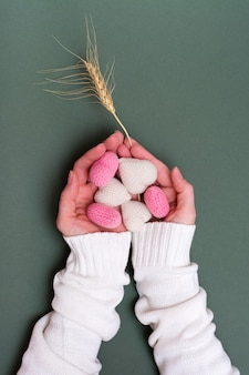 Still life for valentine's day. knitted hearts in female hands and an ear of wheat on a green background. vertical view