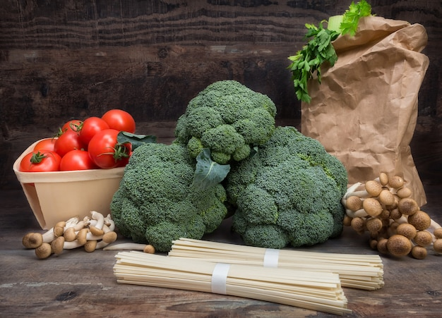 Still life vegetables cabbage broccoli with tomatoes mushrooms spaghetti green leaves wooden