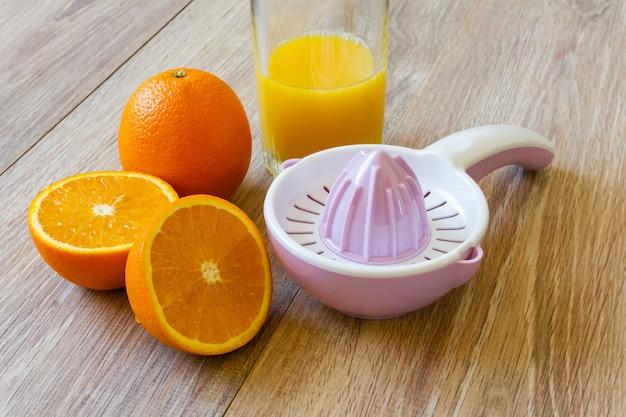 정물 - 나무 탁자에 있는 전체 및 자른 오렌지, 수동 리머 및 오렌지 주스 한 잔