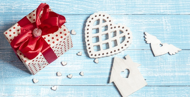 木の表面に美しく包まれた贈り物と装飾的な要素のある静物。バレンタインの休日のコンセプト。