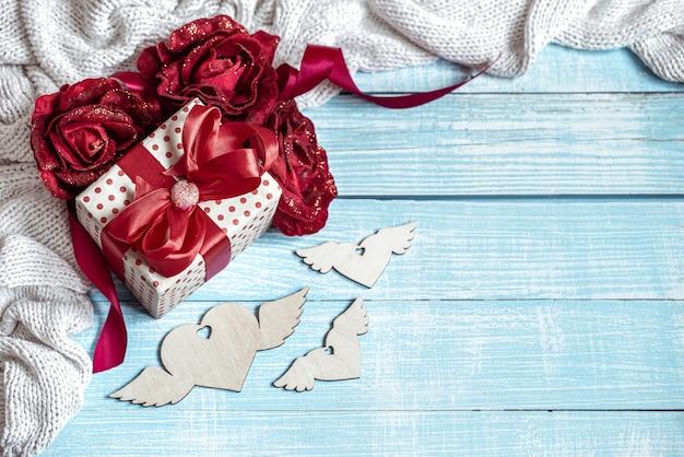 木の表面に美しく包まれた贈り物、花、装飾的な要素のある静物。バレンタインの休日のコンセプト。