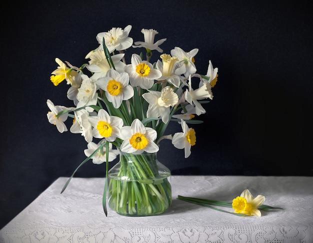 白いテーブルクロスのテーブルの上にガラスの花瓶に水仙の花束と静物。