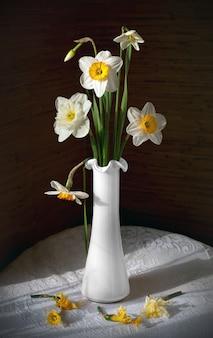 白いテーブルクロスと丸いテーブルの上に白い花瓶の水仙の花束と静物。