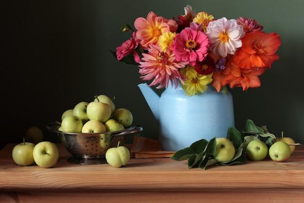 木製のテーブルにダリアと果物の花束のある静物。庭の花と初期の青リンゴ。