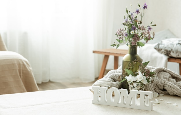花の花束、本、木製の装飾的な言葉の家のある静物。