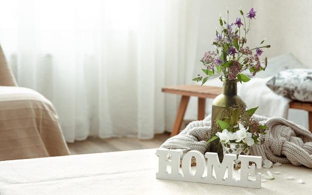 花の花束、本、木製の装飾的な言葉の家のある静物
