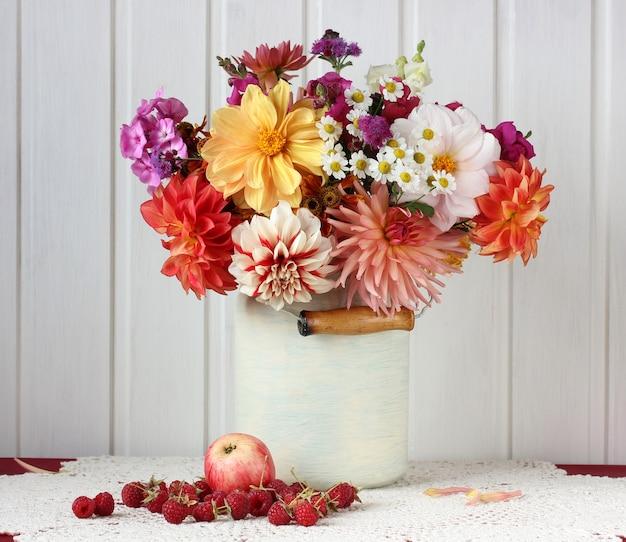 レースのテーブルクロスにガーデンダリア、アップル、ラズベリーの花束のある静物。
