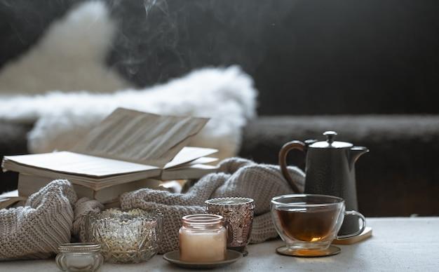 一杯のお茶、ティーポット、本、キャンドル付きの美しいヴィンテージの燭台のある静物。家の装飾の概念。