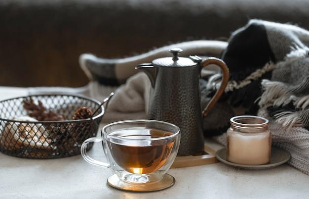 Натюрморт с чашкой чая, чайником, книгой и деталями декора на размытом фоне.