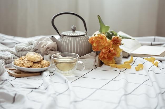 Натюрморт с чашкой чая, чайником, букетом тюльпанов и печеньем в постели. выходные и концепция весеннего утра.