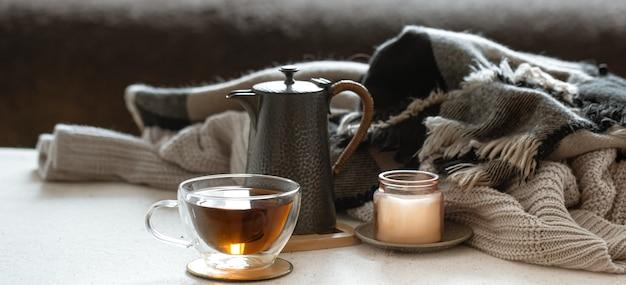 차 한 잔, 찻 주전자, 촛대에있는 촛불 및 니트 물건으로 정물을 닫습니다.