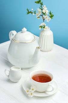 青い背景にお茶、ティーポット、花瓶のある静物。