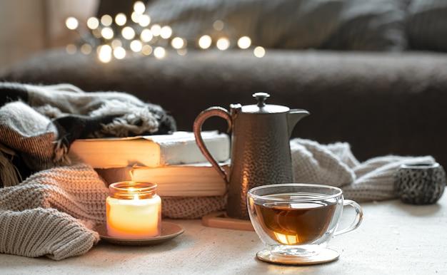 一杯のお茶、ティーポット、本、燭台に燃えるろうそくのある静物
