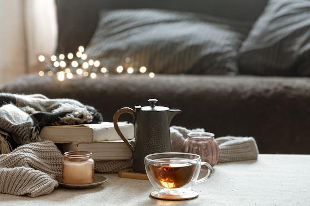 차 한잔, 주전자, 책 및 촛대에 촛불이있는 정물