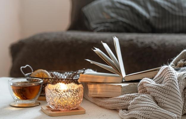 美しい燭台にお茶、本、燃えるろうそくのある静物。ホームコンフォートコンセプト。