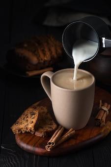 カップケーキとマグカップに牛乳を注ぐ静物