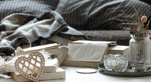 Натюрморт с декоративным сердцем, книги и уютные домашние вещи.