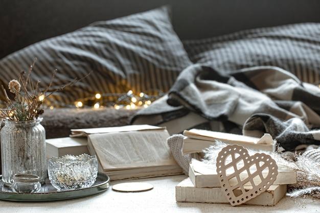 ボケ味のあるぼやけた背景に装飾的な心、本、居心地の良いもののある静物。バレンタインデーのコンセプト。
