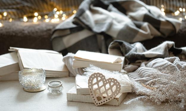 装飾的な心、本、そしてボケ味のある居心地の良いもののある静物。バレンタインデーのコンセプト。