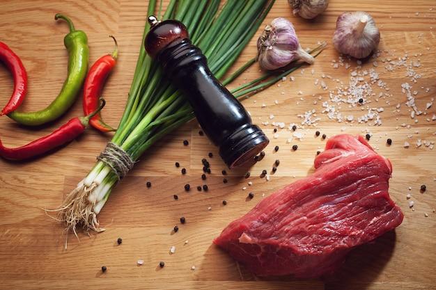 Натюрморт с кусочком свежей говядины, мельницей для перца, чили, чесноком и зеленым луком