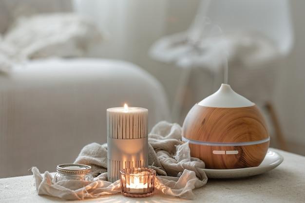 Натюрморт с ароматическим диффузором для увлажнения воздуха и зажженными свечами.