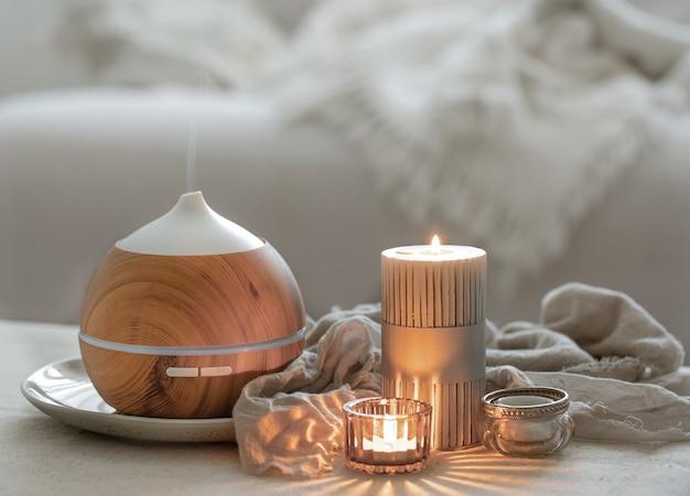 공기를 보습하고 촛불을 태우는 아로마 디퓨저가 있는 정물.