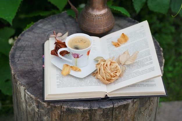 緑の植物で覆われたアンティークピッチャー、開いた本、一杯のコーヒーのある静物