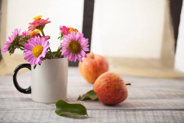 창문 옆 나무 표면에 사과와 꽃이 있는 정물