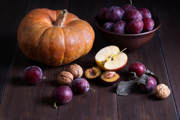 秋の実のある静物。暗い木の表面に新鮮な熟したプラム、カボチャ、リンゴ、クルミ。素朴なスタイル。収穫、秋、健康的でベジタリアン料理のコンセプト。セレクティブフォーカス。
