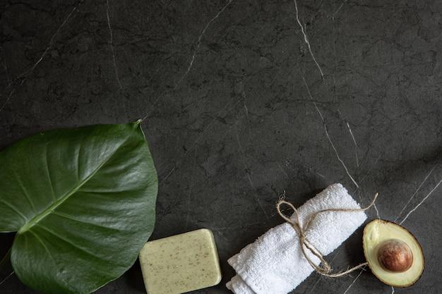 暗い大理石の表面のコピースペースにアボカド、タオル、石鹸のある静物。顔と体のスキンケアのコンセプト。