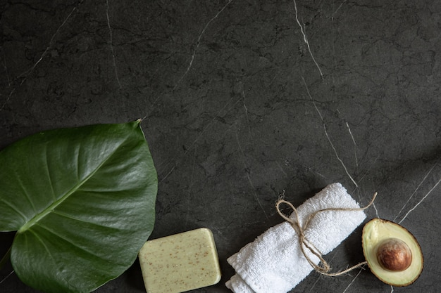 Still life with avocado, towel and soap on a dark marble surface copy space. face and body skin care concept.