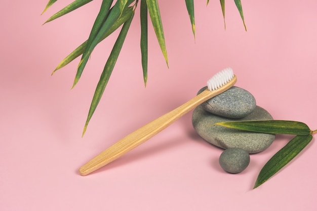 Натюрморт с бамбуковыми зубными щетками, камнями и листьями бамбука на розовом фоне