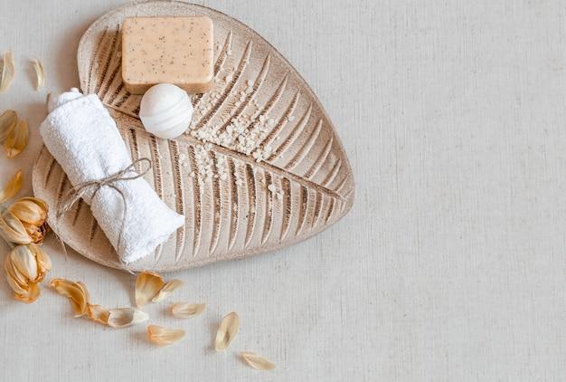 Натюрморт с банными принадлежностями на листовой подставке, вид сверху. уход за телом и концепция гигиены.