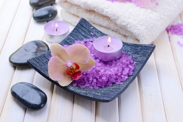 Натюрморт с красивым цветущим цветком орхидеи, полотенцем и миской с морской солью, на цветном деревянном фоне