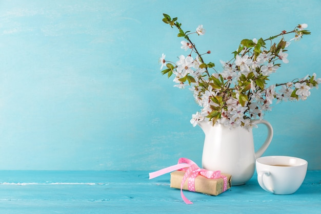 Still life with a beautiful spring cherry blossom flowers, coffee cup and gift box on blue wooden table with copy space