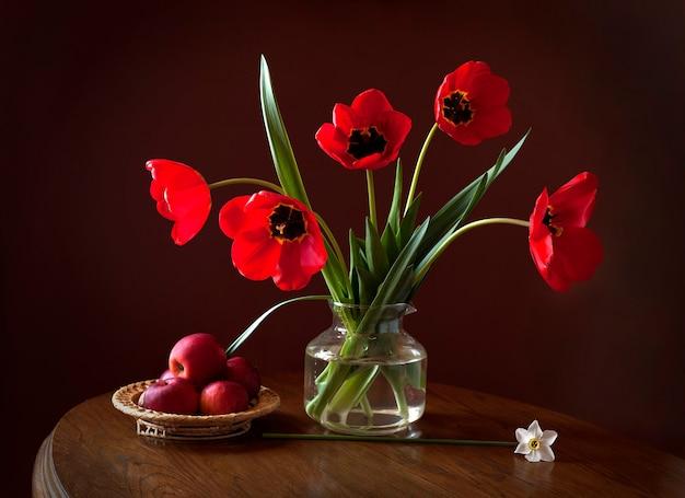 美しいチューリップ、赤いリンゴ、木製のテーブルの上に水仙の花がある静物。