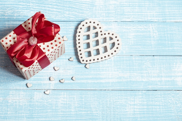 Still life with a beautifully wrapped gift and decorative elements on a wooden surface. valentine's holiday concept.
