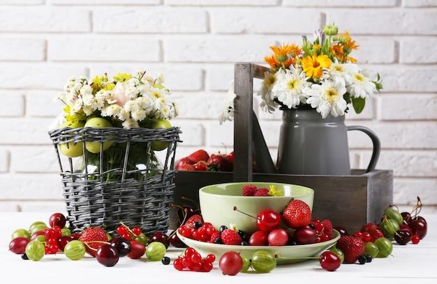딸기와 흰 벽에 꽃 정물화