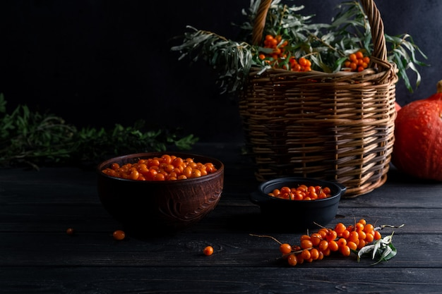 Still life with berries and branches of sea buckthorn, basket on a dark wooden background